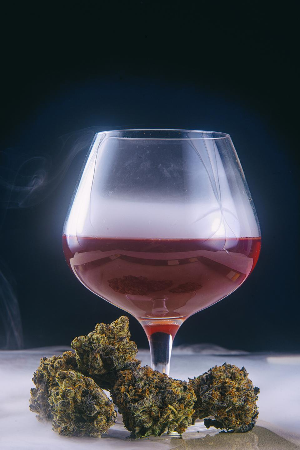Dried cannabis buds (Grandaddy Purple strain) with glass of red wine isolated on black blackground.