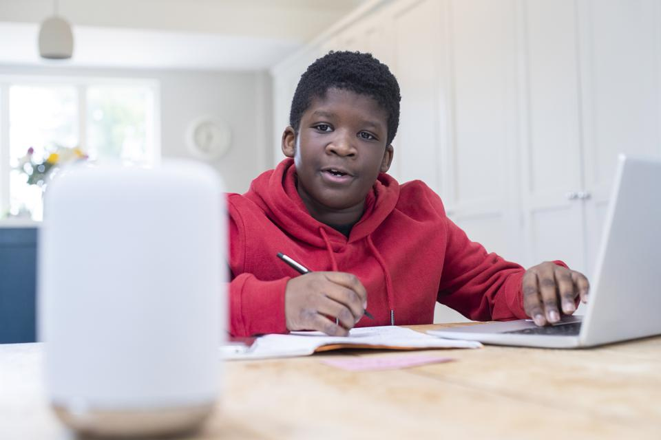 A child is using a smart speaker in his home to help with school work.