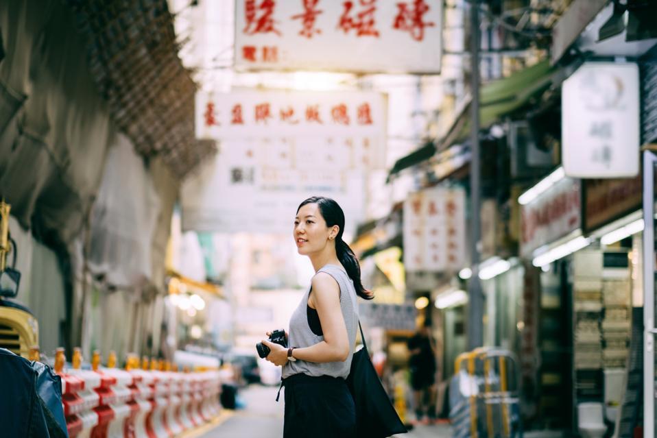 Beautiful young woman carrying camera exploring and walking through local city street