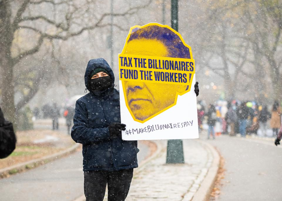 A person holds a sign that reads, ″tax the billionaires, fund the workers″