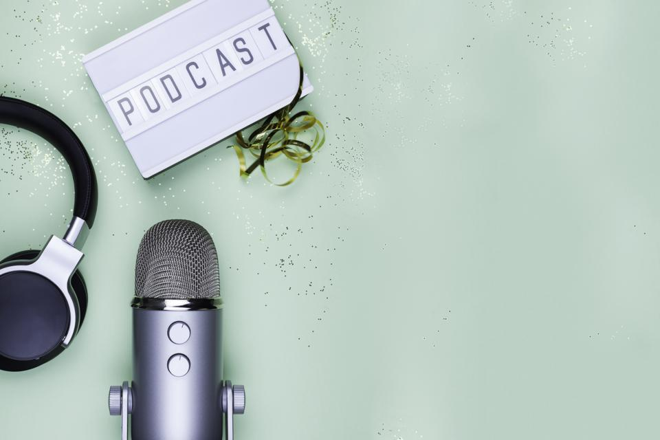 Top view photo of podcast concept - lightbox with letters podcast on it, headphones and professional microphone