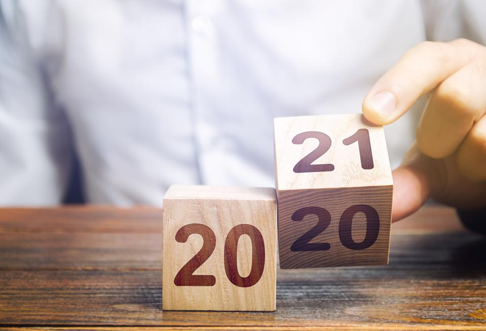 Hand flips a block changing 2020 to 2021. New year beginning. Holidays and Christmas. Trends and changes in the World. Build plans. New normal. Summing work done. Keep up with everything planned.