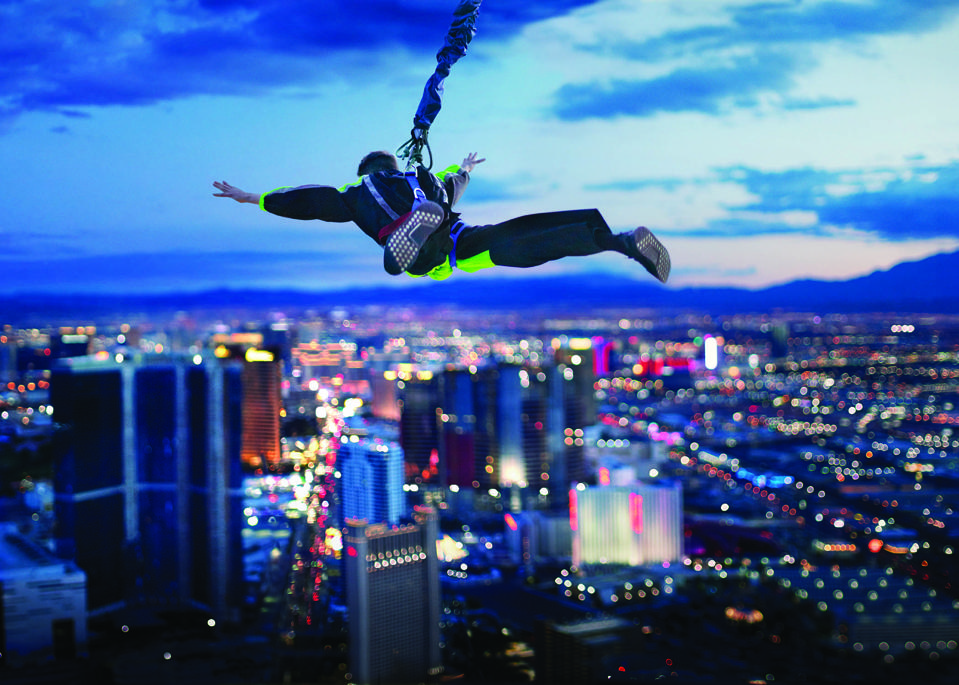 skyjump in harness over las vegas cityscape.