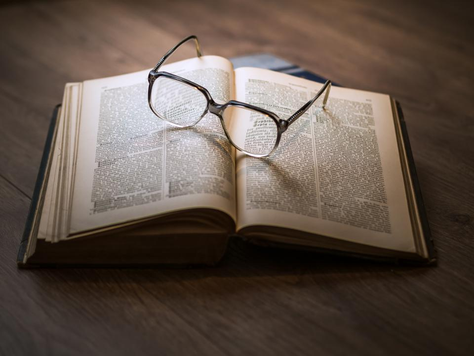 A pair of glasses upon an open book, and the piece is entitled 'The Power of Knowledge'