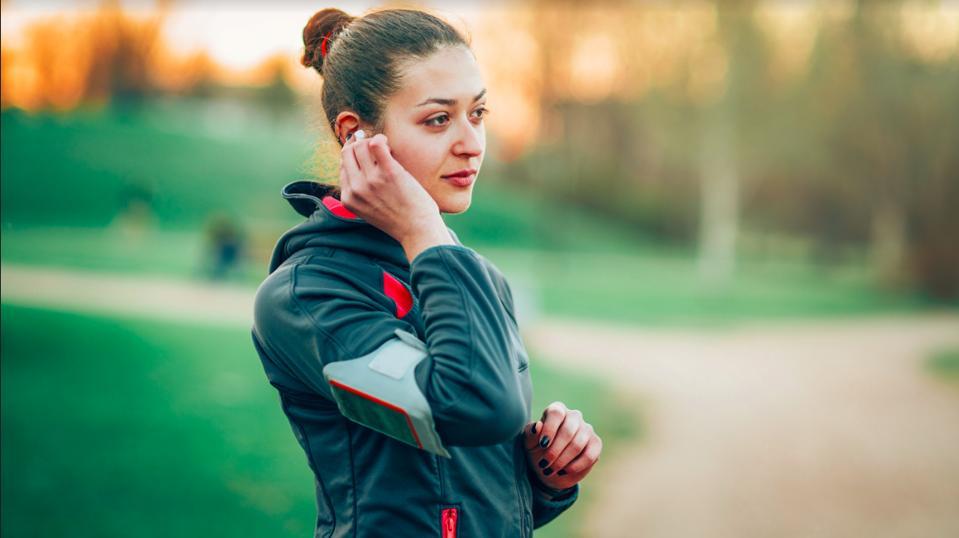 Women preparing to run with her earpods.