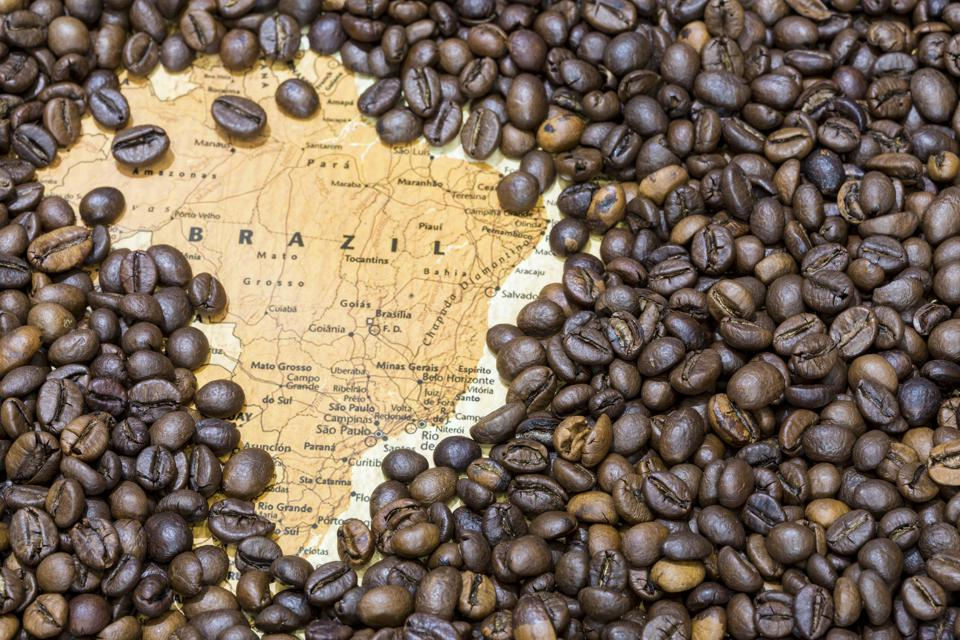 Map of Brazil under a background of coffee beans