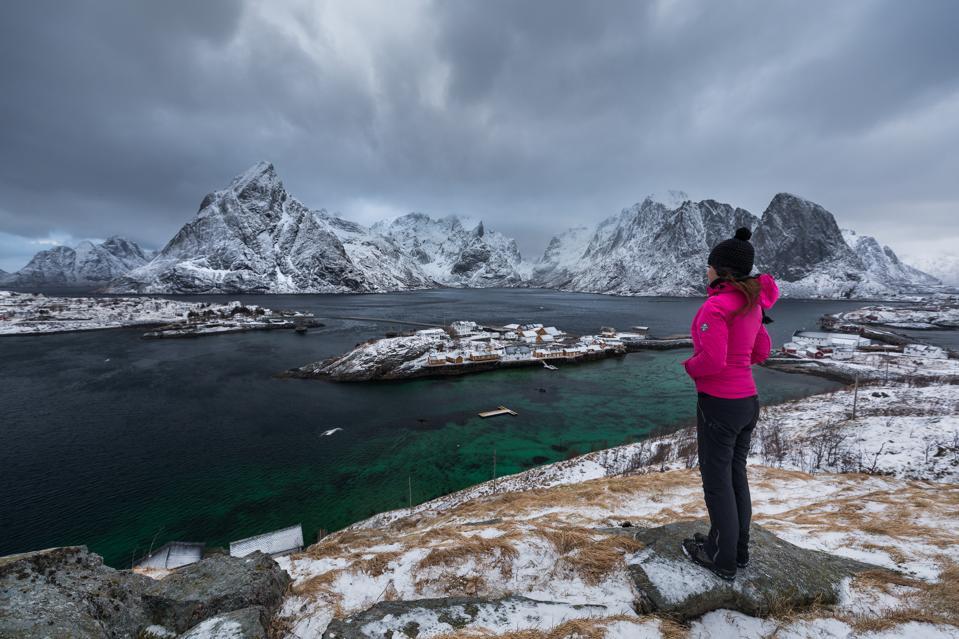 A lone hiker looking over Norway's Lofoten Islands in the winter.