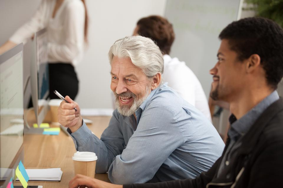 Smiling senior employee discussing email with african colleague at workplace