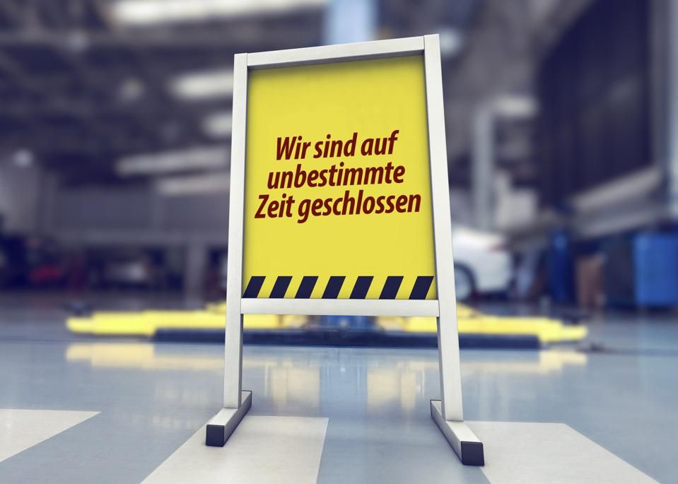 sign in front of the auto repair shop in germany warning that they are closed indefinitely due to corona virus