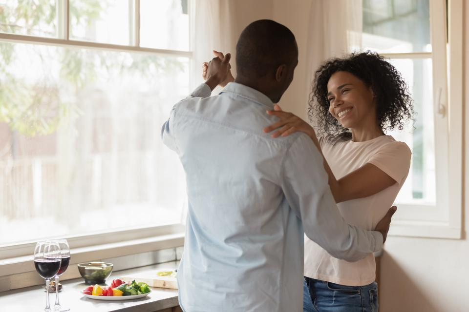 Loving african American couple dancing enjoy date at home