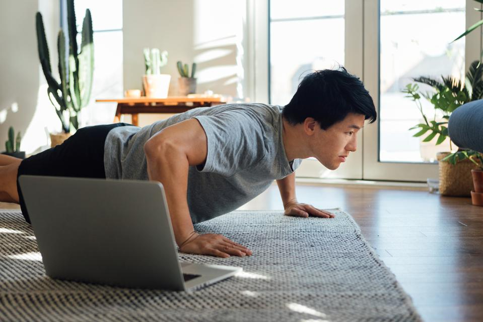 Cropped shot of young man doing push-up in front of laptop at home