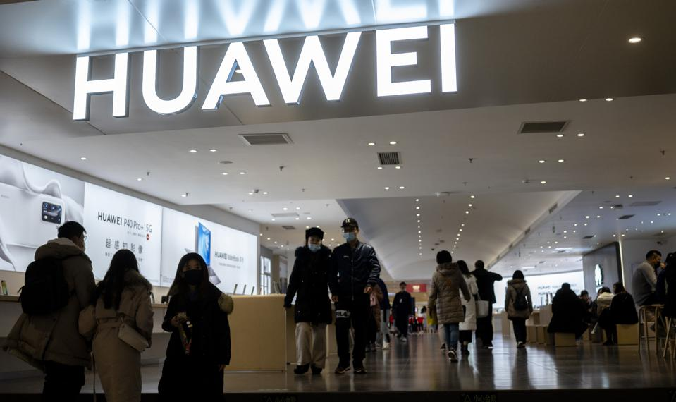 Customers walk into a Huawei store.