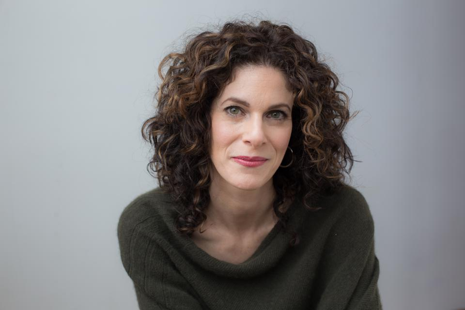 Smiling white woman with brown curly hair wearing olive color sweater.