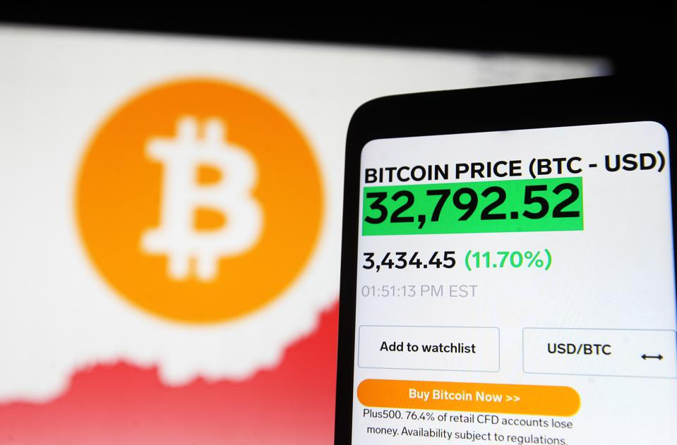 In this photo illustration, a Bitcoin logo, and price seen...
