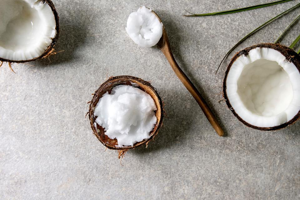 Organic vegan cold pressed coconut oil in coconut and wooden spoon on gray texture background.  Healthy eating.  Flattening.  copy space