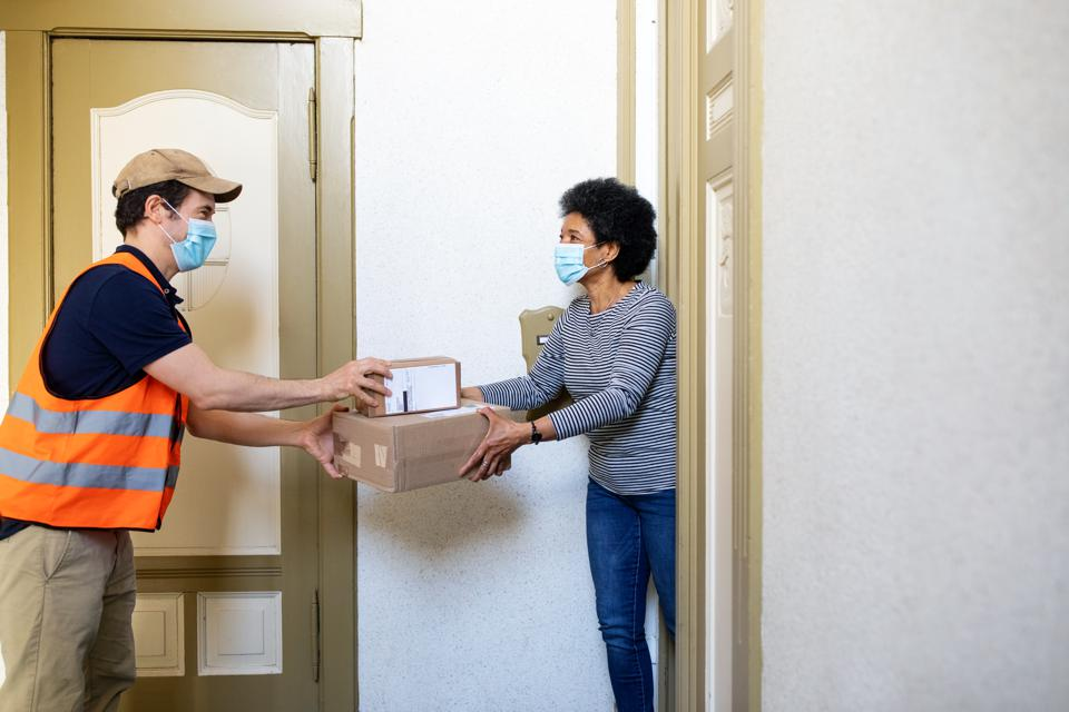 Woman receiving delivery box from courier during self isolation
