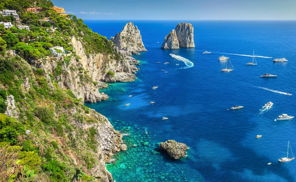 Amazing Faraglioni cliffs panorama with the majestic Tyrrhenian sea in background. Capri island, Campania region, Italy.