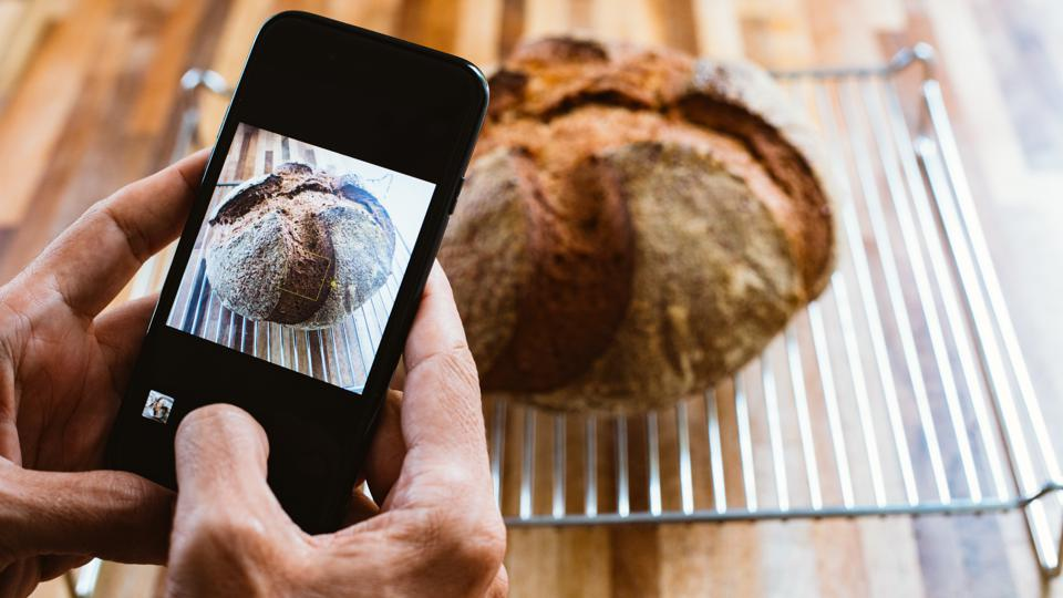 A man taking and sharing the photo of an homemade sourdough bread with mobile / smart phone
