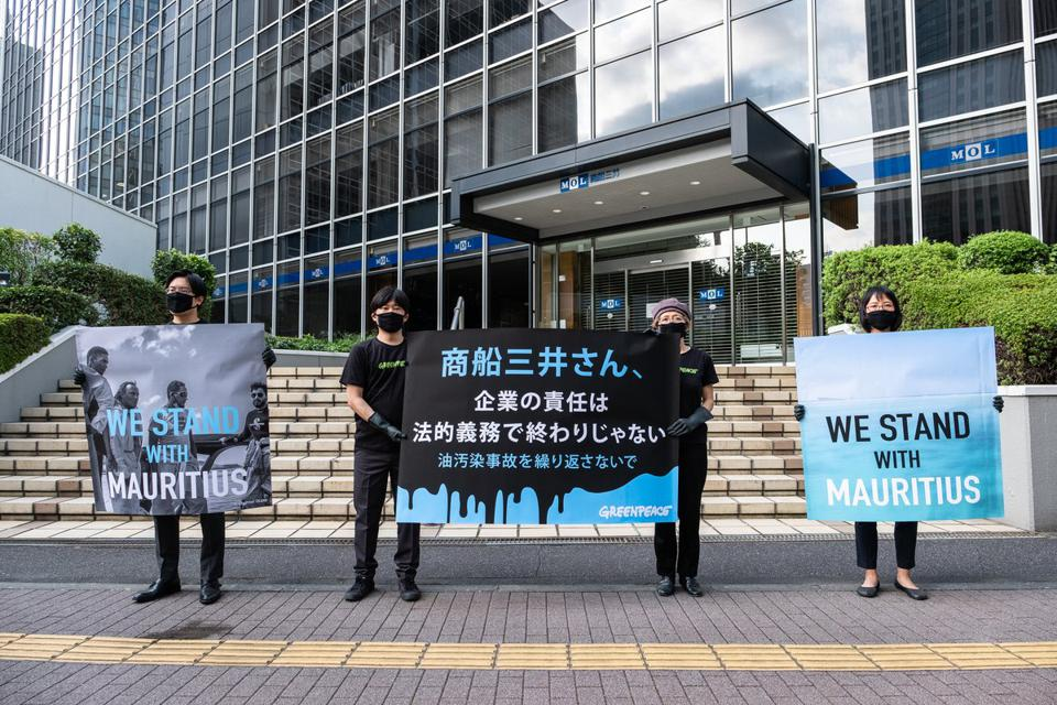 On August 25, one month after the accident, Greenpeace Japan activists held banners at (MOL) headquarters, calling on MOL to fulfill its responsibility.  Poster says 'No more oil, go renewables.'