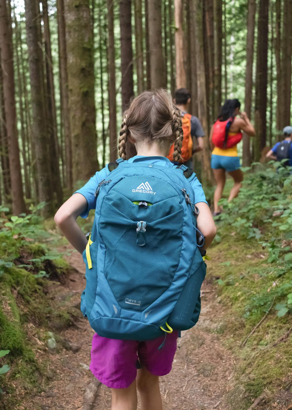 Girl with backpack hiking in the woods