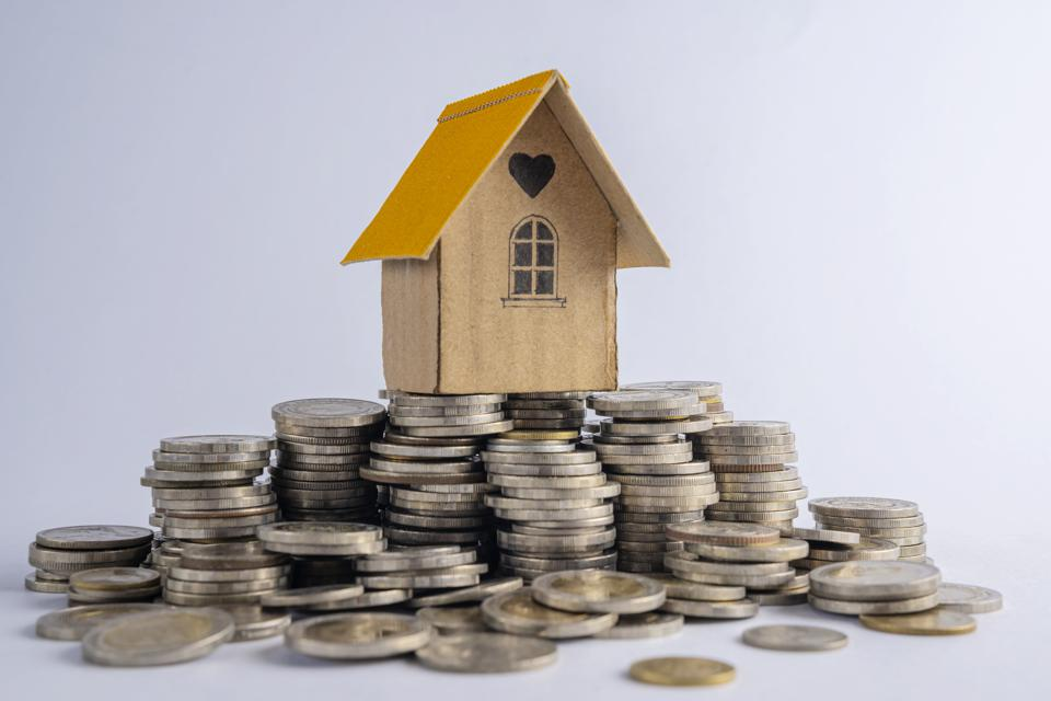 House on a pile of coins. Mortgage real estate concept. Investment, save money or future home.Contracting for housing.