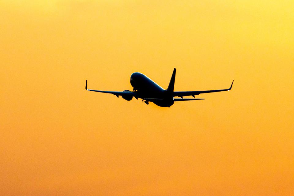 Silhouette of a departing passenger aircraft during a golden sunset.