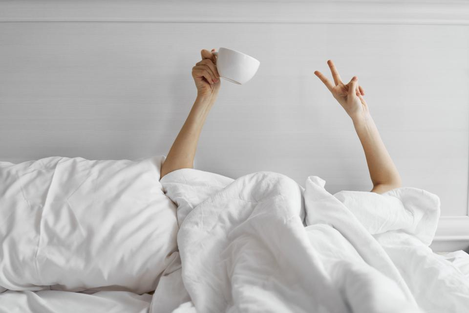 Woman with a mug of coffee in bed