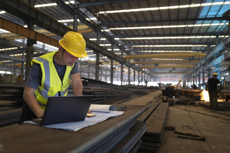 Asian male engineer using laptop in factory