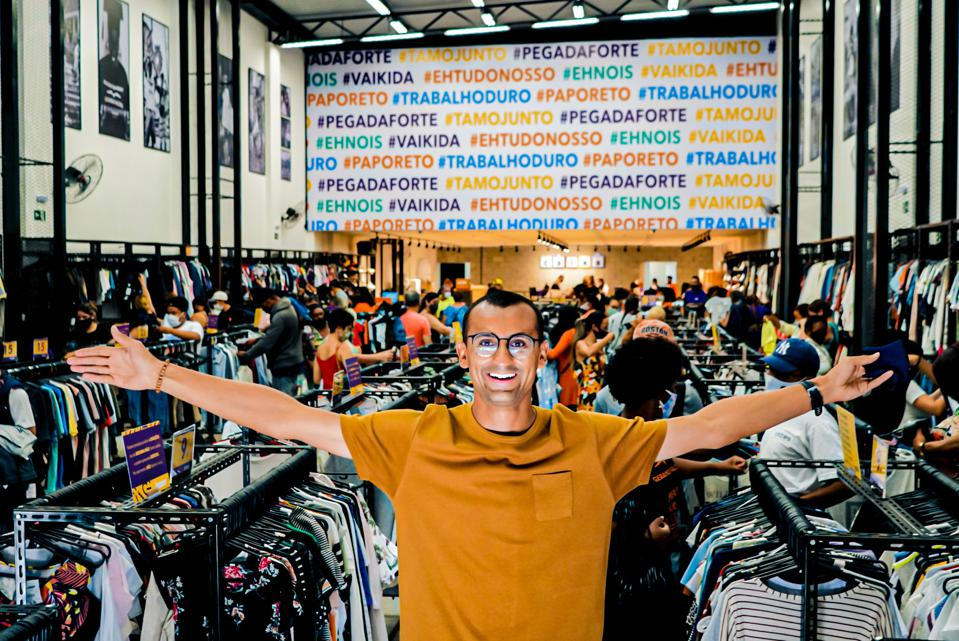 image of a man in a second hand clothers shop with open arms and wearing a yellow shirt