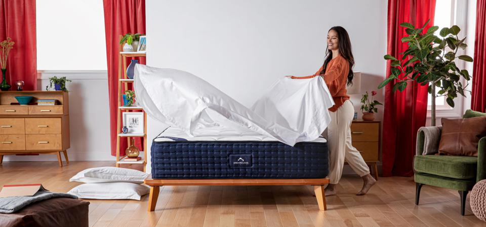 A photo of a woman making a bed with a DreamCloud mattress.