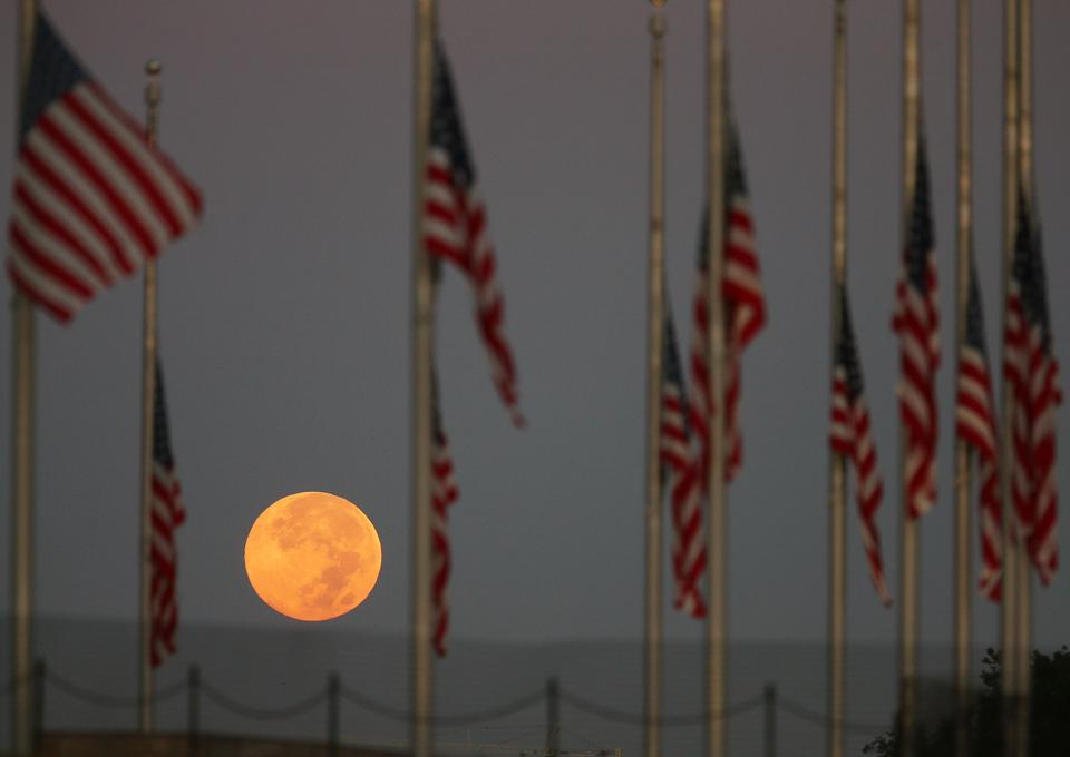 A full moon glows behind flags at the Washington Monument (Photo by Mark Wilson/Getty Images)