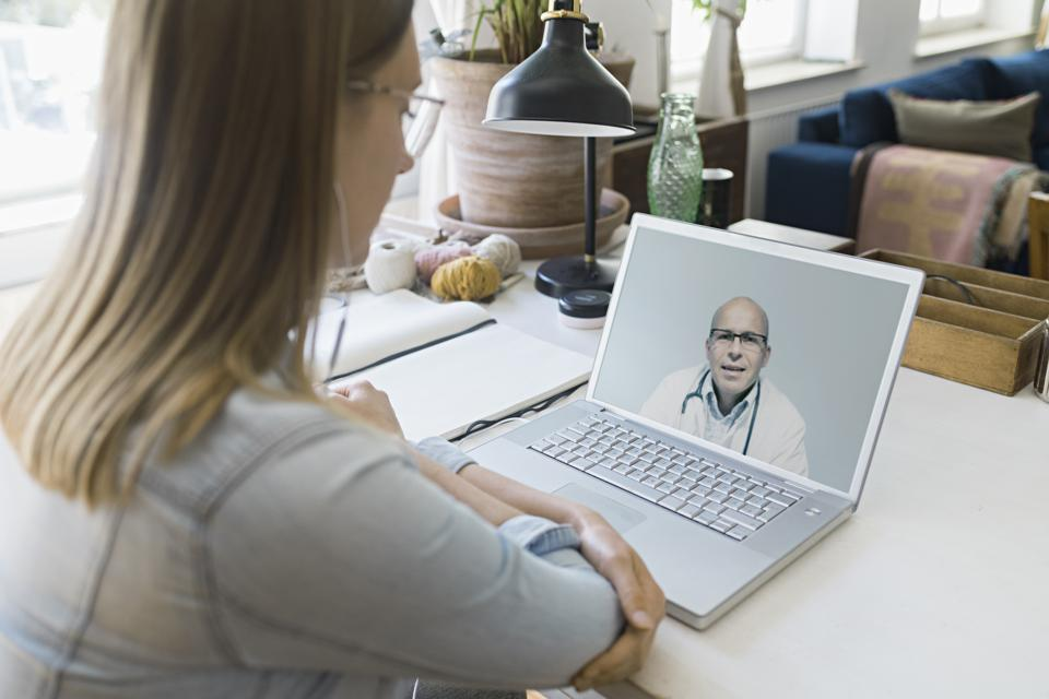young woman talking to doctor on video call