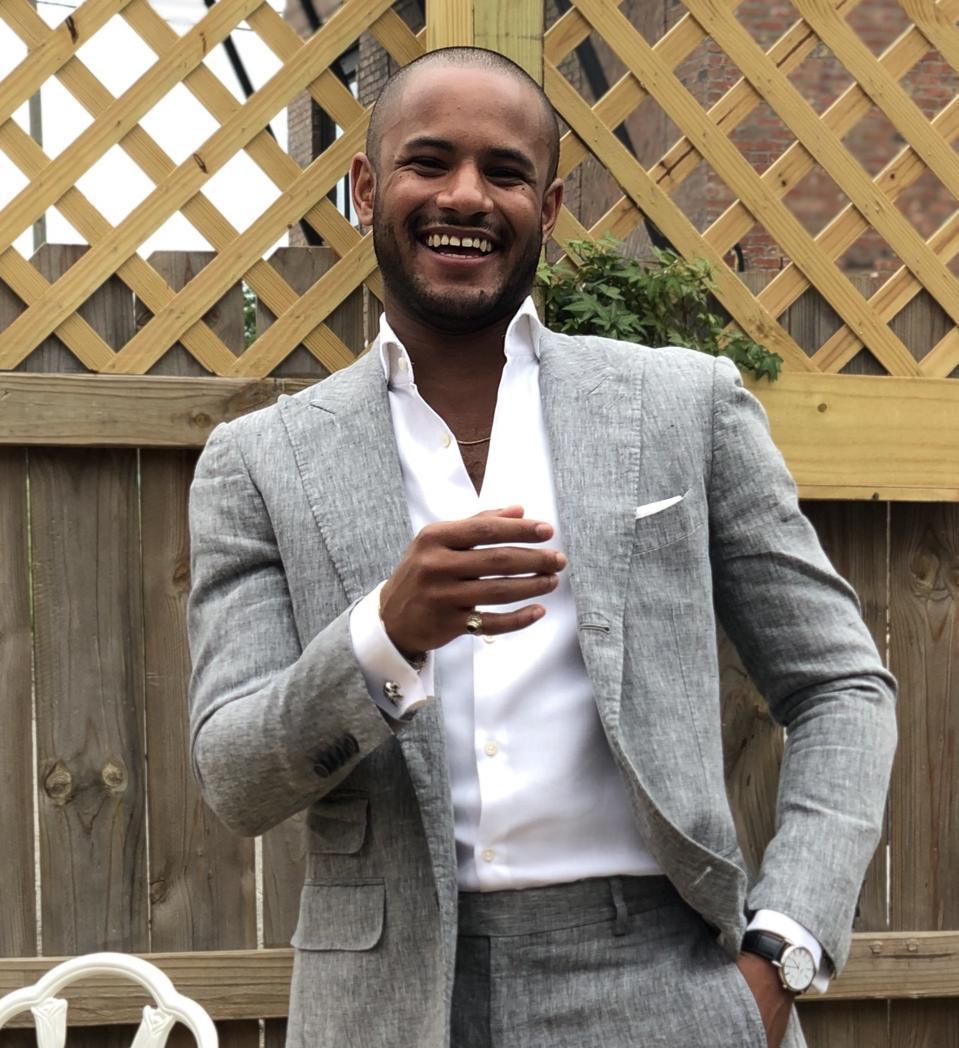 Jamil Karriem in a gray casual suit smiling