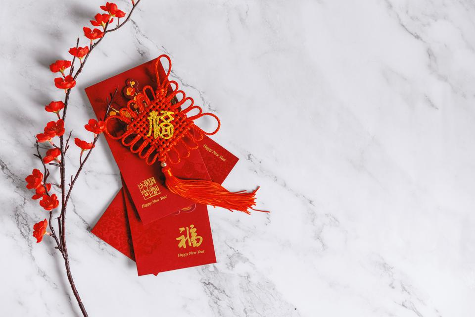 Chinese New Year Background. Red Envelope, Flower and Decoration on White Marble.