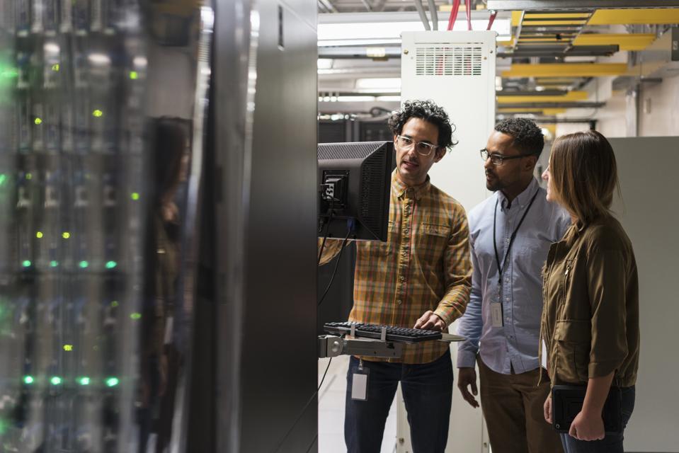 Technicians using computer in server room