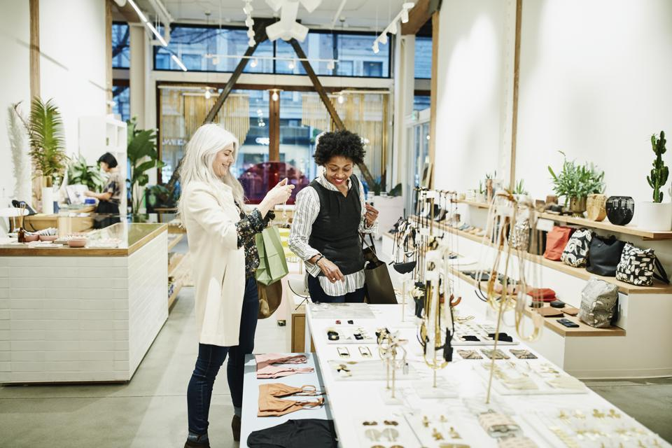 Smiling mature female friends admiring jewelry while shopping together in boutique