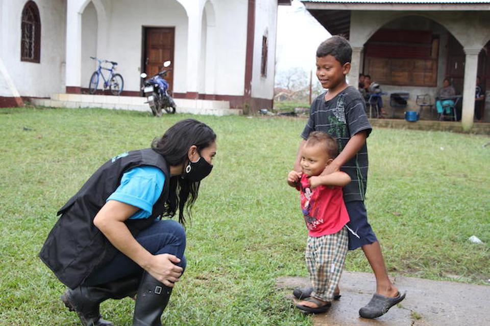 A UNICEF team member visits with children in Nicaragua's Lamlaya community to assess their needs and provide support in the wake of Hurricane Iota.