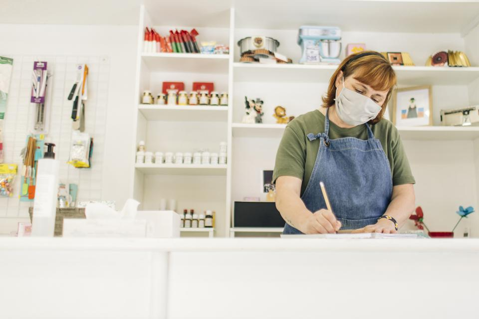 Female baker wearing mask writing in book on checkout counter at shop