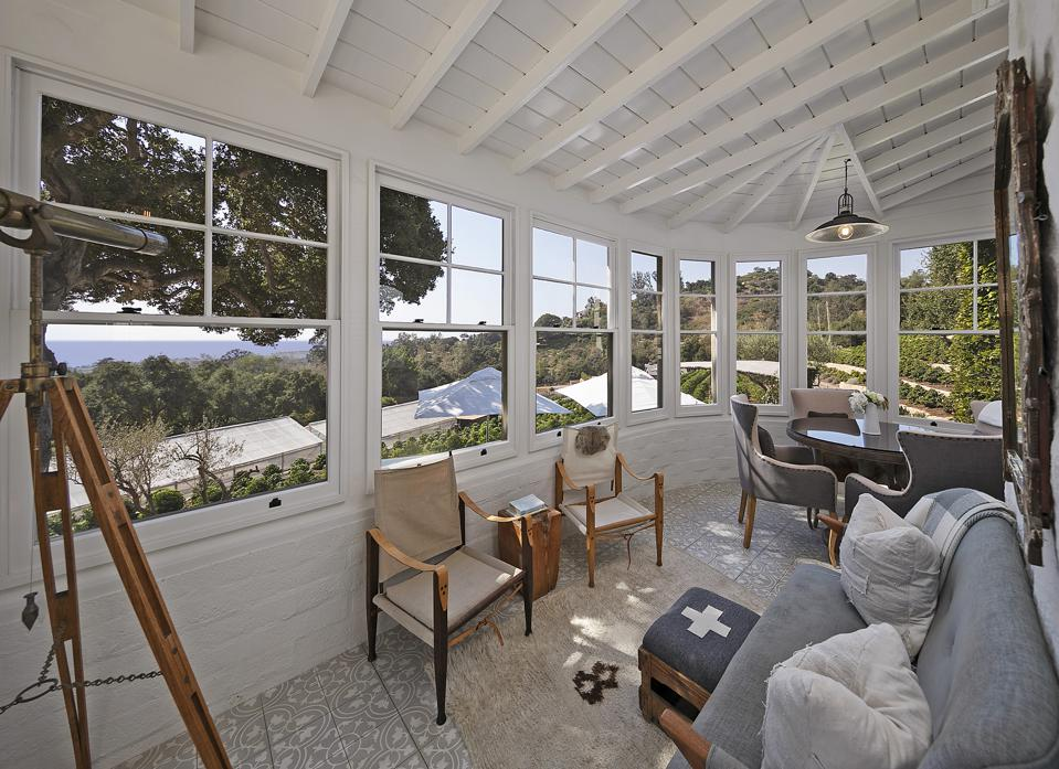 A white sunroom with windows and furnishings looks out onto the landscape and ocean.