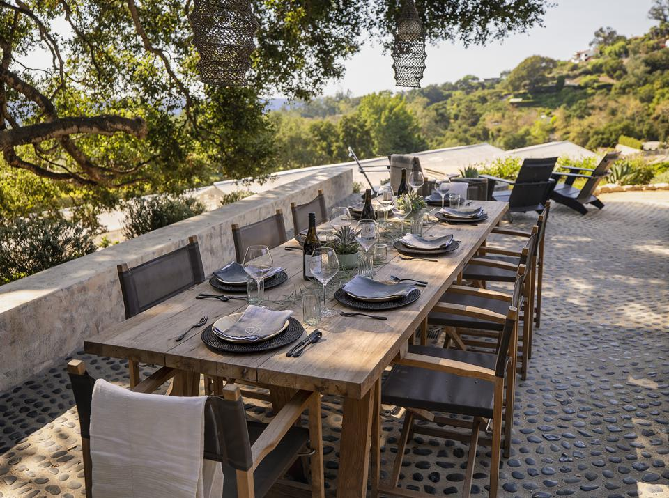 A set dining table provides outdoor seating and views or the ocean and orchards.