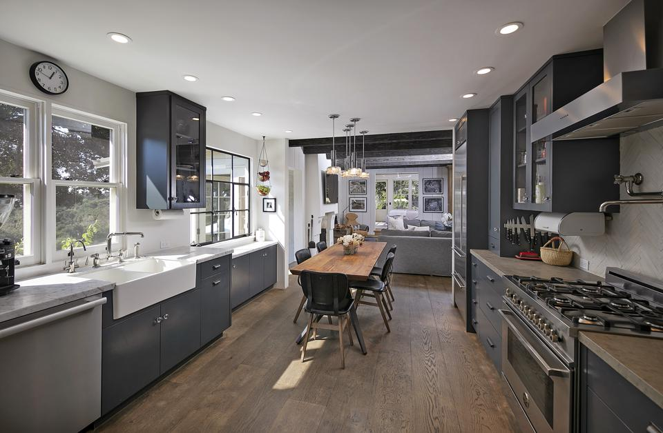 A chef's kitchen features windows, appliances and a dining table.