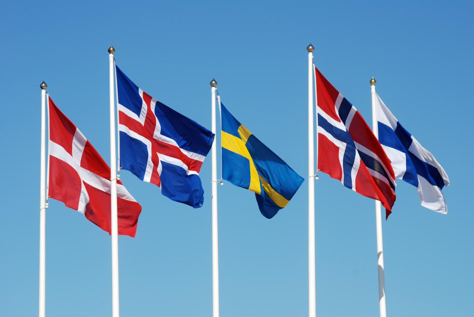 Nordic flags flying against a blue sky.