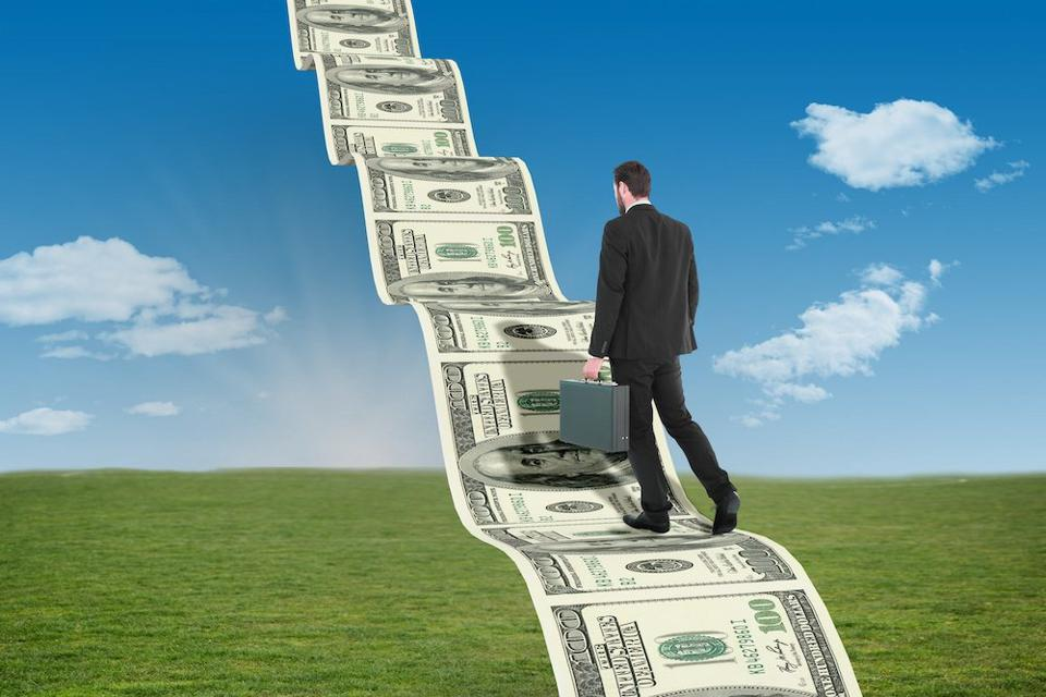 businessman climbing stairway of money into sky