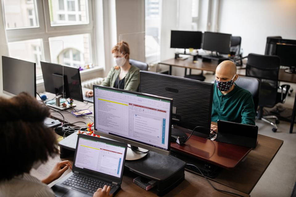 Business people with face mask working in startup office