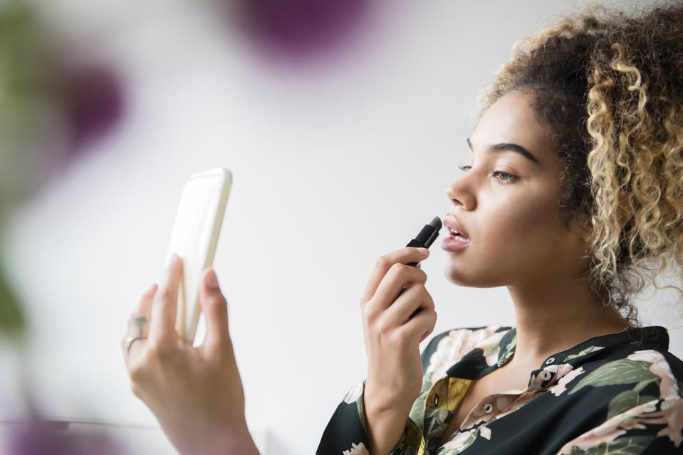 Woman holding cell phone applying lipstick