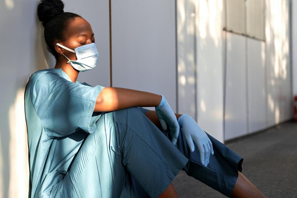 Tired nurse sits on hospital floor.