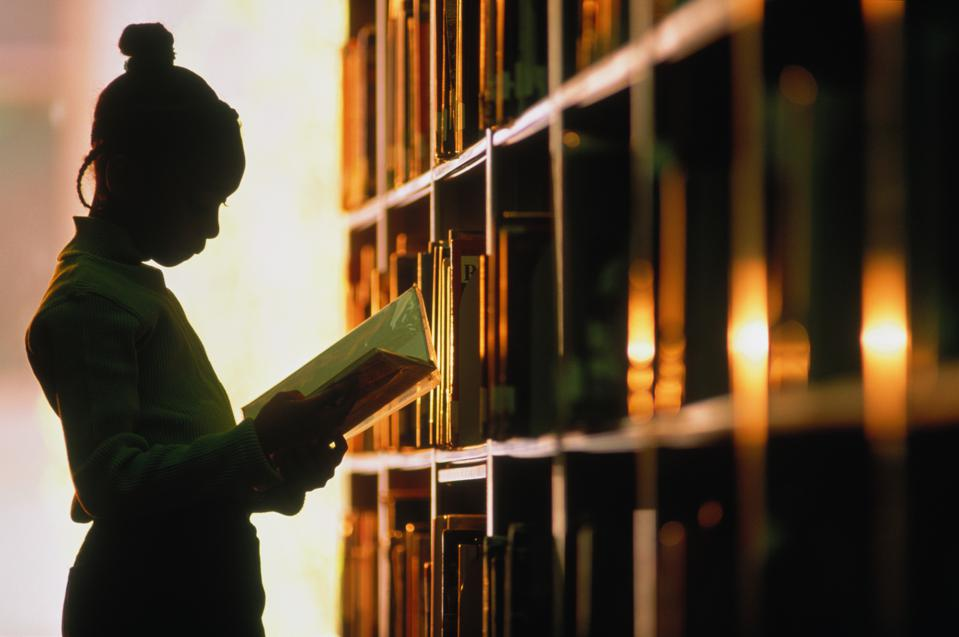 Girl (6-8) looking at book in library, silhouette