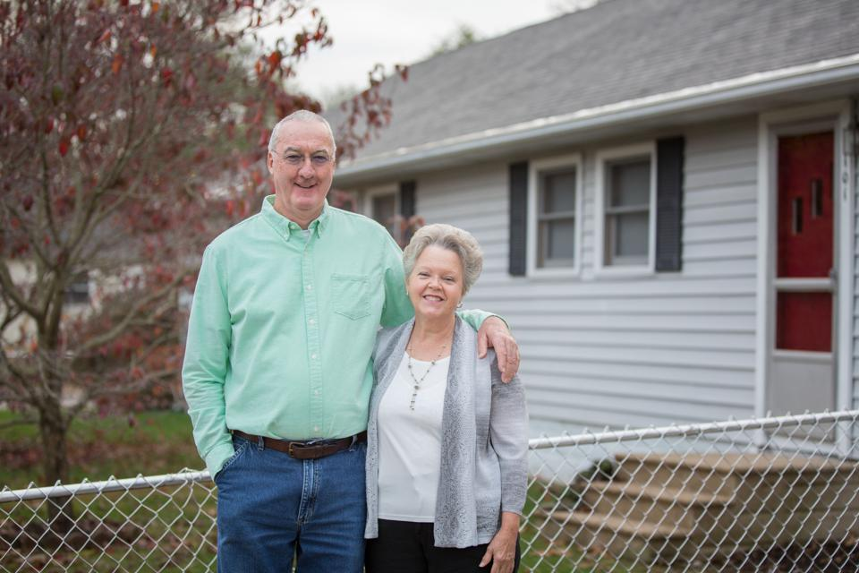 Man and woman standing in front of home