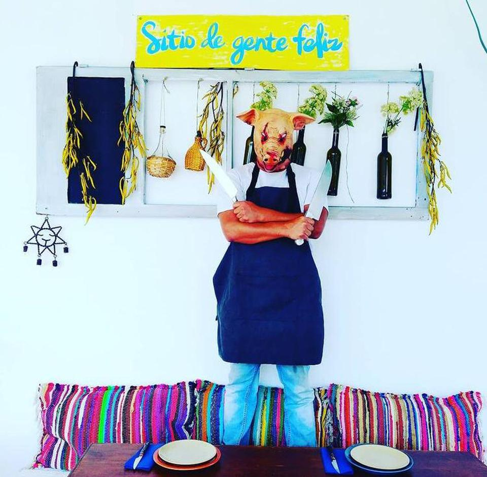 The chef of restaurant Sitio de Gente Feliz in Lisbon wears a pig mask in the dining room