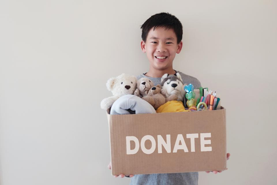 Volunteer holding a box full of used toys, and books